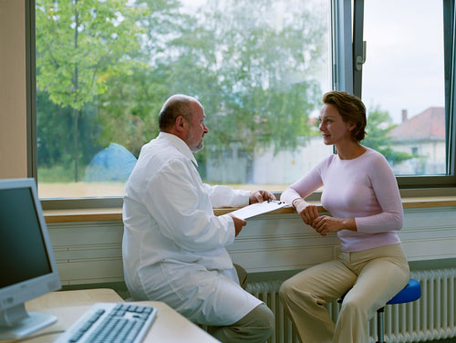 Female patient consulting with male dentist in front of a window
