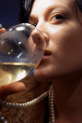 A woman drinking white wine.